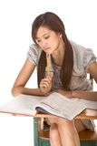 Asian college student preparing for math exam. Asian student girl sitting by the desk and studying huge math book, preparing to test Royalty Free Stock Image