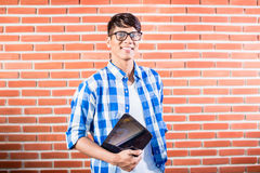 Asian College Student with tablet computer. In front of brick wall stock image
