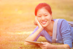 Asian college student use tablet pc Royalty Free Stock Photos