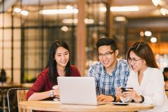 Asian college students group or coworkers using laptop computer together at cafe or university. Casual business, freelance work. Young Asian college students Stock Image