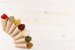 Asian colorful powder spices in rustic paper corner on white wooden board with copy space. Royalty Free Stock Photo