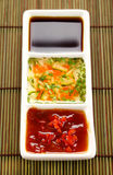 Asian Condiments. Asian dipping sauces consisting of chillie sauce, soy sauce and cucumber and parsley sauce Stock Photo