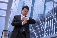 Asian Confident business man watching time for appointment and m. Odern city background , time management concept stock image