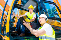 Asian construction driver discussing with engineer blueprints. Asian construction machinery driver discussing with foreman blueprints on pad or tablet computer Royalty Free Stock Photos