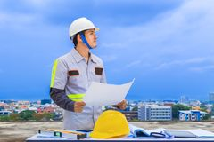 Asian construction engineer holding blueprint at construction si. Te, blue sky and cityscape background Royalty Free Stock Photos