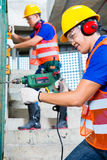Asian construction workers drilling in building walls Royalty Free Stock Photo