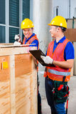 Asian construction workers on site open wood box. Two Asian Indonesian industrial or construction workers controlling with a checklist a delivery on a tower Royalty Free Stock Image