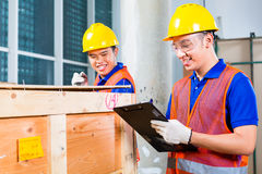 Asian construction workers on site open wood box. Two Asian Indonesian industrial or construction workers controlling with a checklist a delivery on a tower Stock Photography