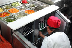 Asian cook in a citchen working on a vegetable buffet bar Stock Photos