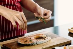 Asian Cook Is Sprinkling Herb On Raw Salmon To Prepare Food On The Modern Kitchen Counter Royalty Free Stock Photos