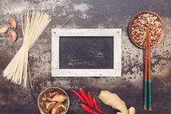 Asian cooking ingredients. With chopsticks on rustic board, blank blackboard for text. Top view, blank space royalty free stock photos