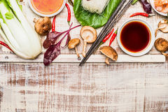Asian cooking ingredients with chopsticks on rustic wooden background, top view. Place for text. Asian food concept stock photo