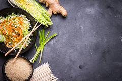 Asian cooking ingredients. Ingredients for making chinese dinner: wheat noodles, rice, napa cabbage, ginger, green onion. Asian cooking ingredients. Top view royalty free stock image