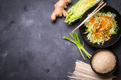 Asian cooking ingredients. Ingredients for making chinese dinner: wheat noodles, rice, napa cabbage, ginger, green onion. Asian cooking ingredients. Top view royalty free stock photo
