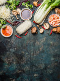 Asian cooking ingredients: rice noodles, pok choy , sauces, shrimps, chili and Shiitake mushrooms on dark background, top view Royalty Free Stock Photography