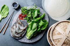 Asian cooking ingredients: rice papper, pok choy, sauces, raw shrimps. Asian food concept Chinese or Thai cuisine. Asian cooking ingredients: rice papper, pok royalty free stock image