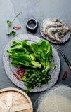 Asian cooking ingredients: rice papper, pok choy, sauces, raw shrimps. Asian food concept Chinese or Thai cuisine. Asian cooking ingredients: rice papper, pok royalty free stock images