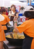 Asian cooks serving food at concessions. Royalty Free Stock Images