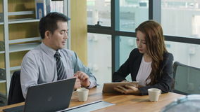 Asian corporate executives discussing business in office. Two asian corporate executives discussing business in office using laptop computer and digital tablet stock video