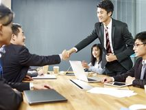 Asian corporate executives shaking hands. Two asian corporate executives shaking hands over negotiation table stock images