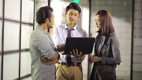 Asian corporate people discussing business in office. Three asian corporate executives discussing business using laptop computer in office