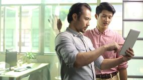 Asian corporate people discussing business in office. Two asian corporate executives discussing business using tablet computer in office stock footage