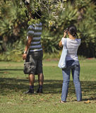 Asian Couple. She is photographing him taking a photo of flowers Royalty Free Stock Photography