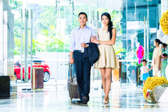 Asian couple arriving in hotel. Lobby Stock Images