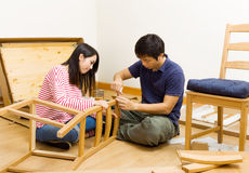 Asian couple assembling chair Royalty Free Stock Images