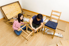 Asian couple assembling furniture for new house Stock Photos