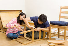 Asian couple assembling new chair Royalty Free Stock Photo