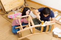 Asian couple assembling new chair Royalty Free Stock Photography