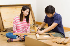 Asian couple assembling new furniture Stock Images