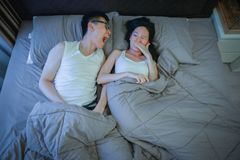 Asian couple with bad breath issues on bed at night stock photo