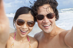 Asian Couple at Beach Taking Selfie Photograph. Man & women Asian couple, boyfriend girlfriend in bikini, taking vacation selfie photograph at the beach Royalty Free Stock Image