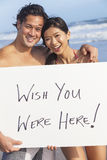 Asian Couple at Beach Wish You Were Here Sign. Man & women Asian couple, boyfriend and girlfriend in bikini, on vacation beach holding Wish You Were Here sign royalty free stock photography