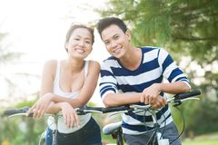 Asian couple with bicycles. Smiling Asian couple with bicycles looking at the camera Stock Photos