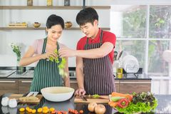 Asian couple They both made a happy salad together in the kitchen at home. royalty free stock photos
