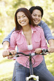 Asian couple both sitting on one bicycle in park Stock Photo