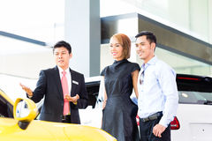 Asian couple buying car in dealership Royalty Free Stock Photo