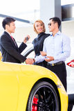 Asian couple buying car in dealership Stock Images