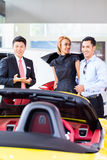 Asian couple buying car in dealership Royalty Free Stock Images