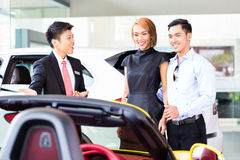 Asian couple buying car in dealership Royalty Free Stock Photography