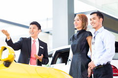 Asian couple buying car in dealership Stock Image