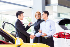 Asian couple buying car in dealership Royalty Free Stock Image