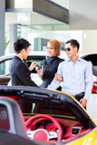 Asian couple buying car in dealership Stock Photo