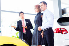 Asian couple buying car in dealership Stock Photography