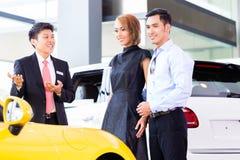 Asian couple buying car in dealership. Asian couple buying car in auto dealership consulting the salesman Stock Photos