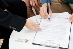 Asian couple buying new house sign contract with realtor at new home,Close up hand of couple purchase apartment.  royalty free stock images