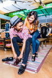 Asian couple buying shoes in store Royalty Free Stock Photo
